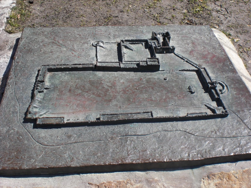 A brass relief of the fort - the mission towards the back